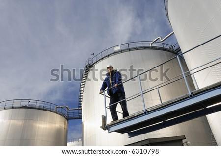 engineer overlooking oil-storage-tanks, sunlight reflecting in tanks - stock photo
