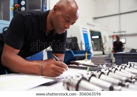 Engineer Planning Project With CNC Machinery In Background - stock photo
