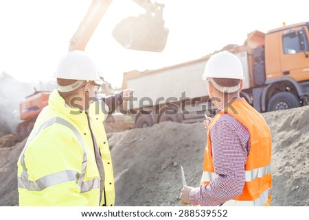 Engineer pointing at vehicles while discussing at construction site - stock photo