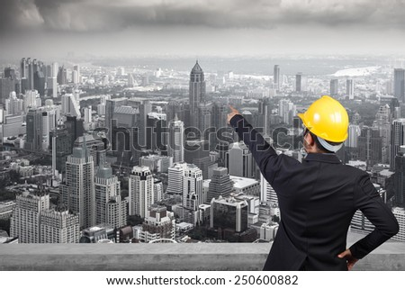 engineer pointing to high building of city in real estate concept - stock photo