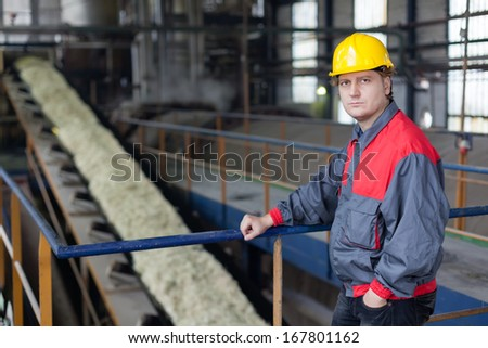 Engineer posing in the front of sugar production line  - stock photo