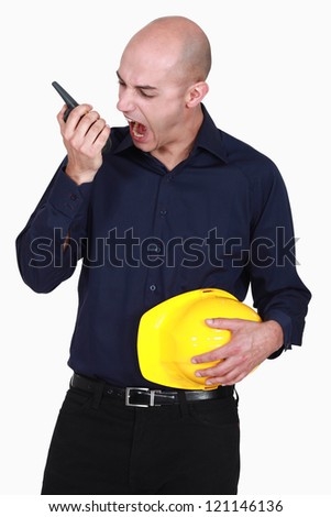 Engineer screaming into a walkie-talkie - stock photo