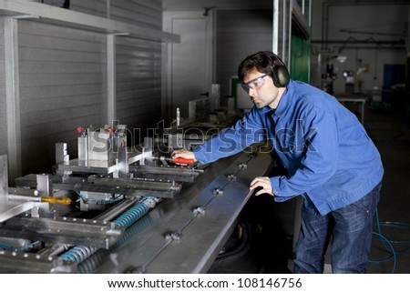 Engineer sets a machine at factory