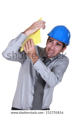 Engineer shielding himself from a blow - stock photo