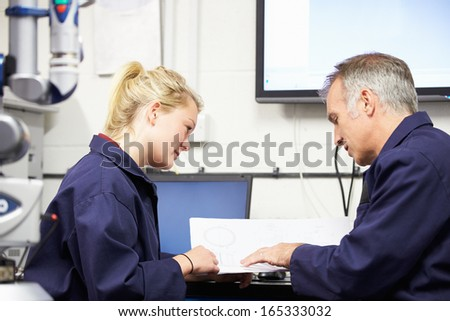 Engineer Showing Trainee Plans With CMM Arm In Foreground - stock photo