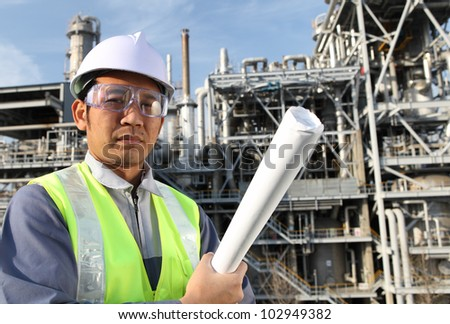 engineer standing in front of a large oil refinery with blueprint on the hand