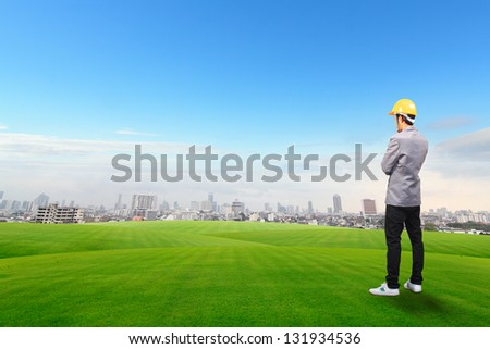 Engineer standing, on green grass field with Building background - stock photo