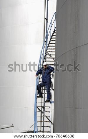 engineer standing on stairs alongside industrial fuel storage tank - stock photo