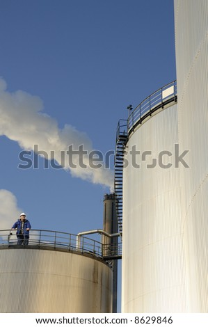 engineer standing on top of refinery oil tanks, smoke and blue-sky in background - stock photo