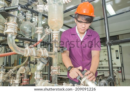Engineer student turning pipeline pump for training in laboratory - stock photo