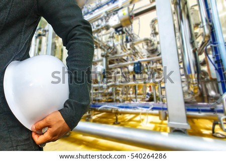 engineer suit white helmet for security stood on the details of Industrial equipment stainless