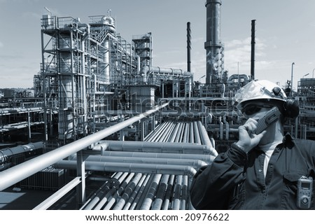 engineer talking in phone, large oil, gas and fuel industry in background, blue toning concept - stock photo