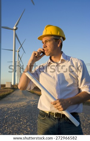 Engineer Talking on Cell Phone in Front of Modern Wind Turbines - stock photo