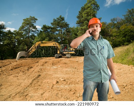 engineer talking on the phone on construction site - stock photo
