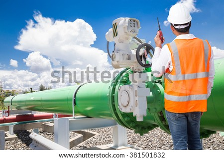 Engineer talking on the walkie-talkie for controlling pipeline valves of cooling water system at thermal power plant - stock photo