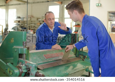 Engineer talking to apprentice over machine - stock photo