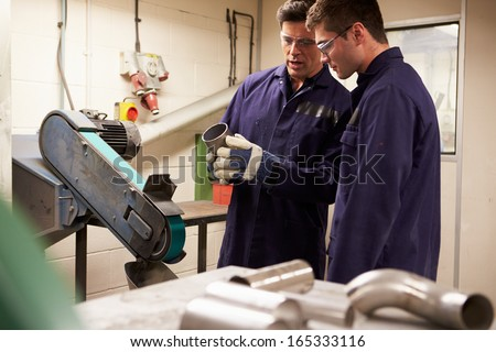 Engineer Teaching Apprentice To Use Grinding Machine - stock photo