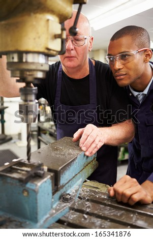Engineer Teaching Apprentice To Use Milling Machine - stock photo