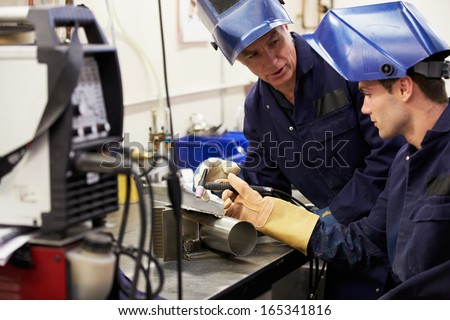 Engineer Teaching Apprentice To Use TIG Welding Machine - stock photo