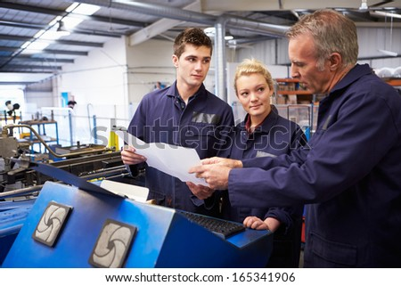 Engineer Teaching Apprentices To Use Tube Bending Machine - stock photo