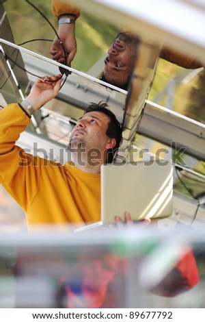 Engineer using laptop and connecting wires at work place - stock photo