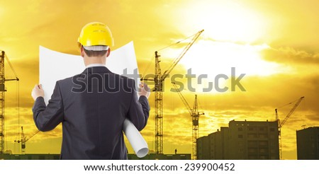 engineer wear yellow helmet for workers security look in blue print on background of new highrise apartment buildings and construction cranes of evening sunset cloudy sky Silhouette Crane lifts load - stock photo