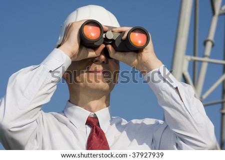 Engineer with binoculars on construction site - stock photo