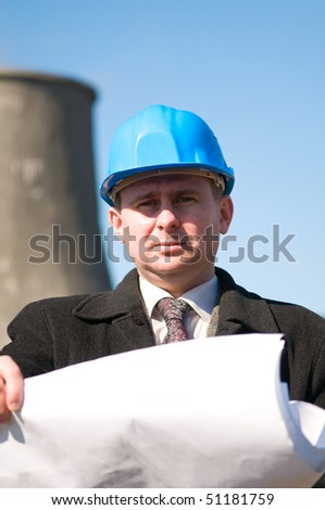 Engineer with blue hard hat holding drawing in industrial area - stock photo