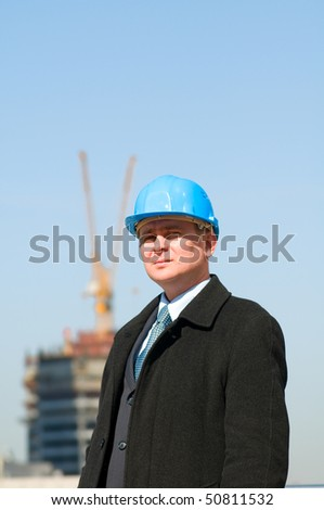 Engineer with blue hard hat on the background of sky and crane - stock photo