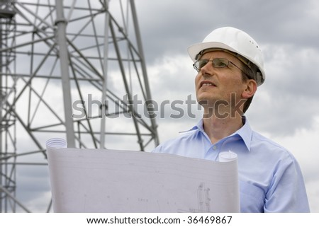 Engineer with blueprint in front of crane - stock photo