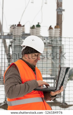 Engineer with computer near the electricity substation - stock photo