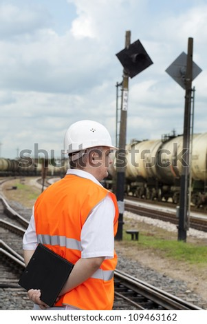 Engineer with folder at the station near the wagons - stock photo