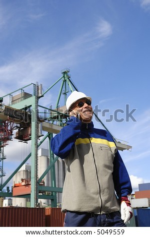 engineer with mobile-phone inside container-port, containers and crane in background