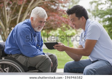 Engineer with muscular dystrophy and diabetes in his wheelchair talking with design engineer using tablet - stock photo