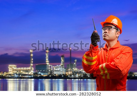 Engineer with radio communication in action for working at oil refinery petrochemical industrial plant at twilight - stock photo