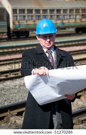 Engineer with white hard hat holding drawing near train - stock photo