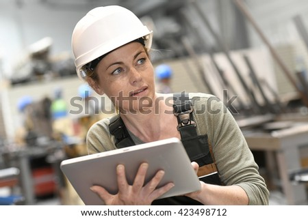 Engineer woman in warehouse checking production
