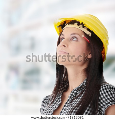 Engineer woman in yellow helmet looking up - stock photo