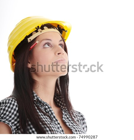 Engineer woman in yellow helmet looking up isolated on white background - stock photo