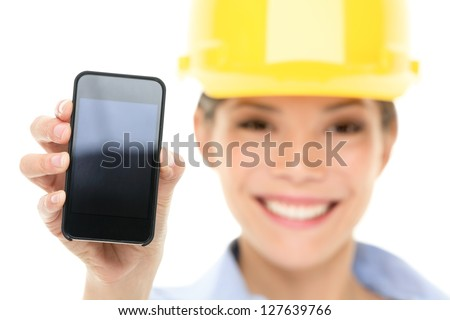 Engineer woman showing smart phone wearing construction hard hat. Young female mixed race Asian / Caucasian female professional isolated on white background. - stock photo