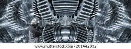 engineer, worker, pointing at a giant surreal gears machinery mirrored in titanium background - stock photo