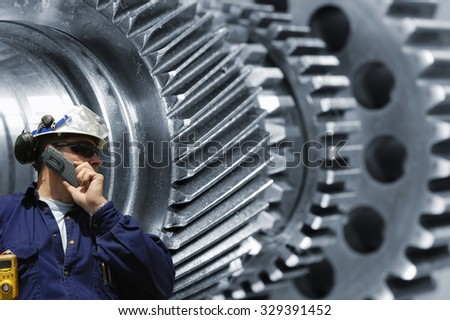 engineer, worker with gears and axles machiney in background, metal bluish toning concept - stock photo