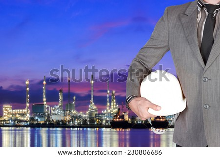 Engineer working at oil refinery petrochemical industrial plant at twilight - stock photo