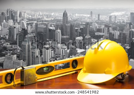 engineer working table and measure tape and level water tool equipment on a high rise structure against urban scene balcony over looking city  - stock photo