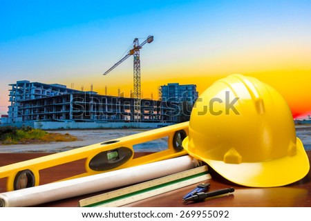 engineer working table plan and blueprint at building construction site against beautiful sky sunset - stock photo