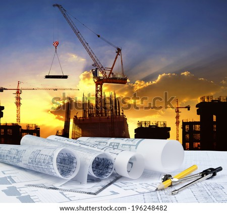 engineer working table plan, and pencil compass against building construction crane with evening dusky sky  - stock photo