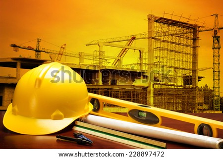 engineer working table plan and writing tool equipment against building construction crane with beautiful sunset - stock photo