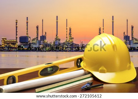 engineer working table plan at petrochemical oil refinery in sunrise - stock photo