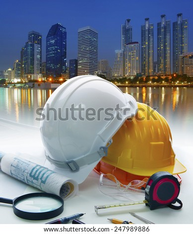 engineer working table with safety helmet and writing equipment against beautiful lighting of building in urban scene - stock photo