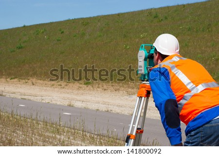 Engineer working with a modern theodolite or total station on a tripod - stock photo